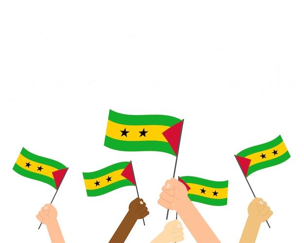 Manos sosteniendo banderas de santo tomé y príncipe