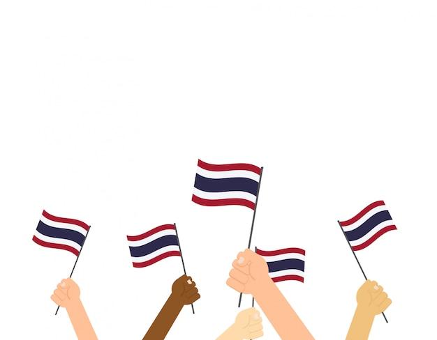 Manos sosteniendo banderas de tailandia