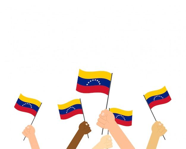 Manos sosteniendo banderas de venezuela