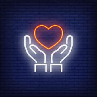 Manos sosteniendo corazón letrero de neón