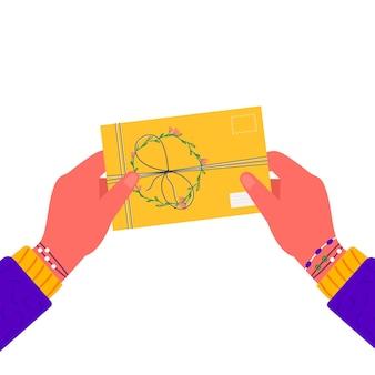 Manos sosteniendo sobre con sellos. mujer enviando carta escrita o correspondencia a través del servicio postal. regalo hecho a mano o presente con carta de papel artesanal, cinta, ramas y otros elementos decorativos.