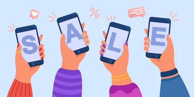 Manos sosteniendo teléfonos inteligentes con venta de palabra en pantalla