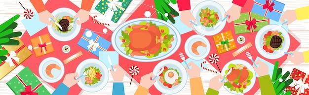 Manos sosteniendo tenedor y cuchillo comiendo comida en la mesa de la cena de año nuevo de navidad pato asado y guarniciones concepto de celebración de vacaciones de invierno vista de ángulo superior ilustración de banner horizontal