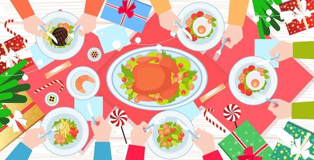 Manos sosteniendo tenedor y cuchillo comiendo comida en navidad año nuevo mesa de cena pato asado y guarniciones concepto de celebración de vacaciones de invierno vista de ángulo superior ilustración