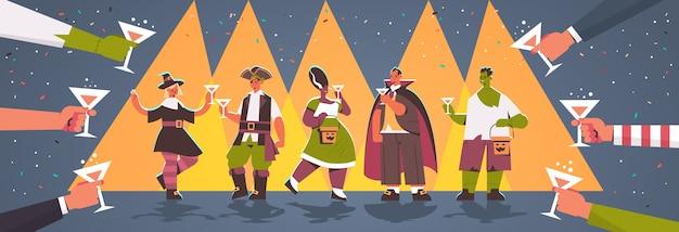 Manos sosteniendo vasos alrededor de personas en diferentes disfraces celebrando el concepto de fiesta de halloween feliz mezcla raza hombres mujeres divirtiéndose tarjeta de felicitación ilustración vectorial horizontal de longitud completa