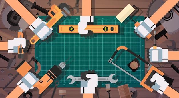Manos sujetando herramientas de reparación y construcción de equipos de trabajo