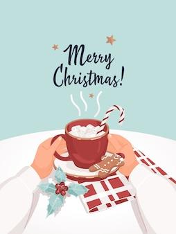 Manos con taza de cacao y texto feliz navidad