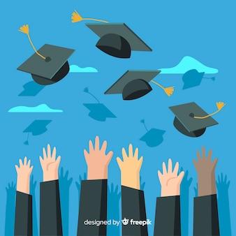 Manos tirando sombreros de graduación al aire