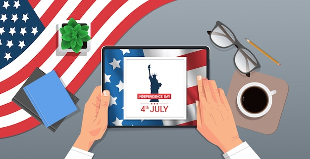 Manos usando tableta con estatua de la libertad en la pantalla 4 de julio concepto de celebración del día de la independencia americana lugar de trabajo vista de ángulo superior ilustración horizontal