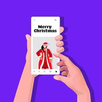 Manos usando un teléfono inteligente con santa mujer en la pantalla año nuevo navidad vacaciones celebración coronavirus cuarentena autoaislamiento concepto ilustración