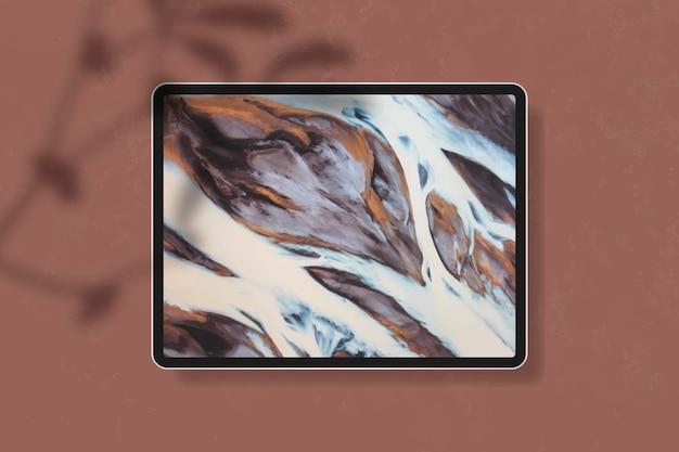 Maqueta de tableta digital en mesa marrón