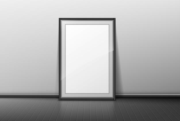 Marco en blanco sobre fondo de pared gris. borde vacío para foto o soporte de imagen en piso de madera en habitación u oficina.