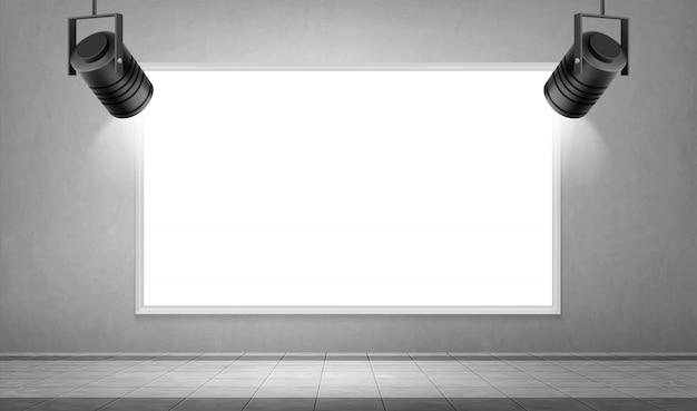 Marco blanco vacío y focos colgantes en museo