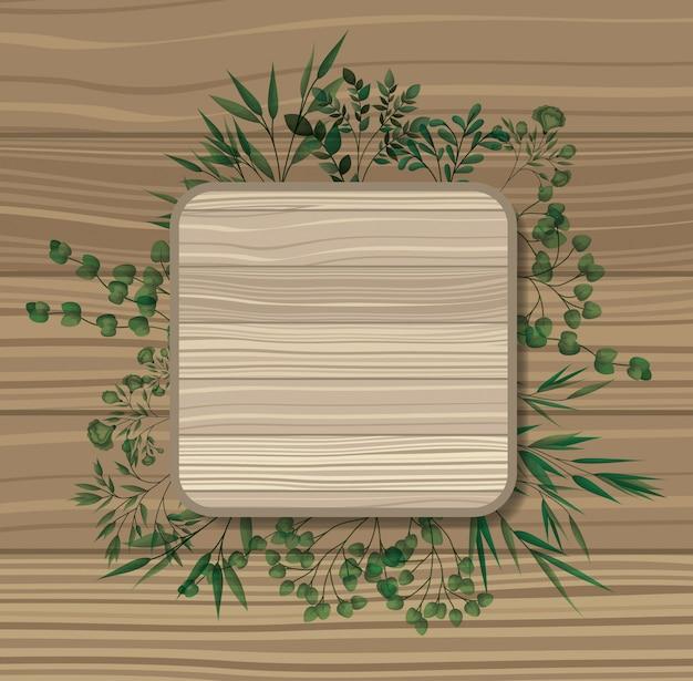 Marco cuadrado con hojas de laurel, fondo de madera.