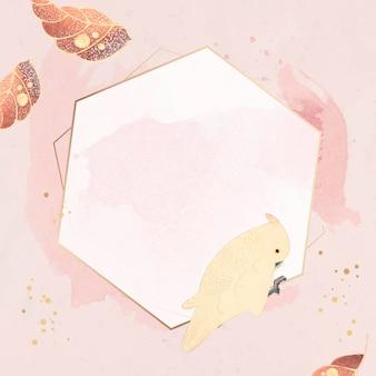 Marco dorado hexagonal con motivos de guacamayos y hojas sobre un fondo rosa pastel