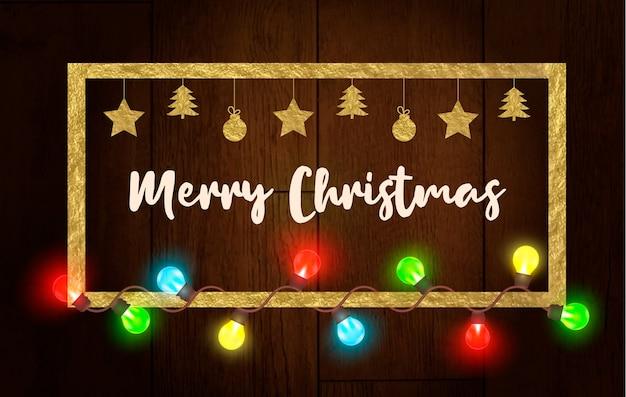 Marco dorado de navidad con guirnalda ligera sobre fondo de textura de madera.