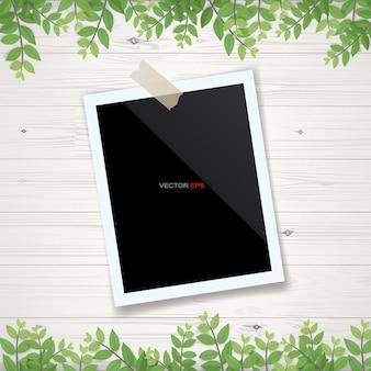 Marco de fotos en blanco o marco de fotos con encuadre de hojas verdes y fondo de textura de madera