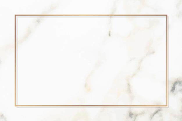 Marco de oro rectangular sobre un mármol blanco