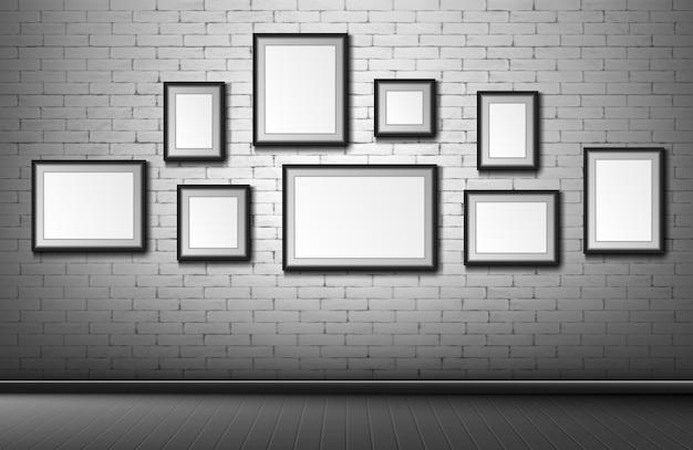 Marcos en blanco en la pared de ladrillo gris