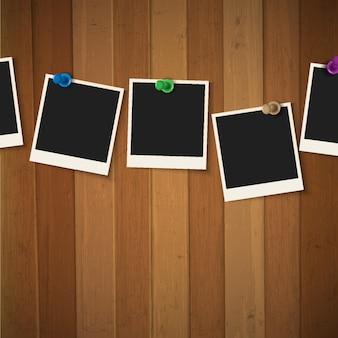 Marcos de fotos con chinchetas de colores sobre fondo de madera