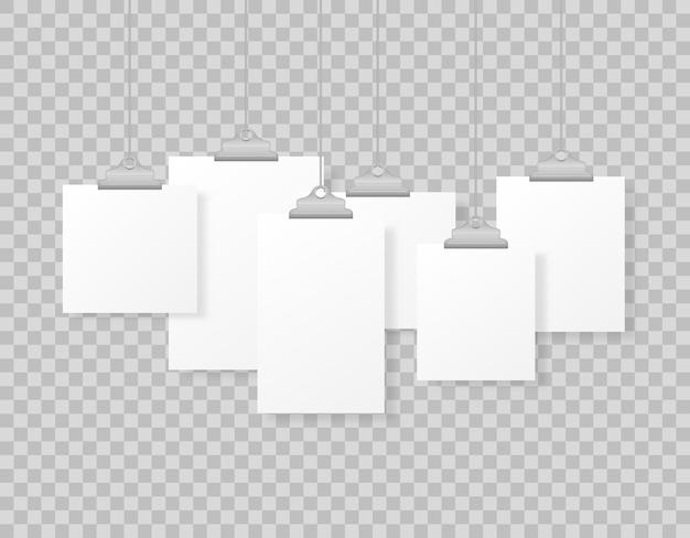 Marcos de fotos colgantes en blanco o plantillas de carteles aislados en el fondo. un conjunto de maquetas de carteles blancos colgados en una carpeta en la pared. marco para una hoja de papel. ilustración.