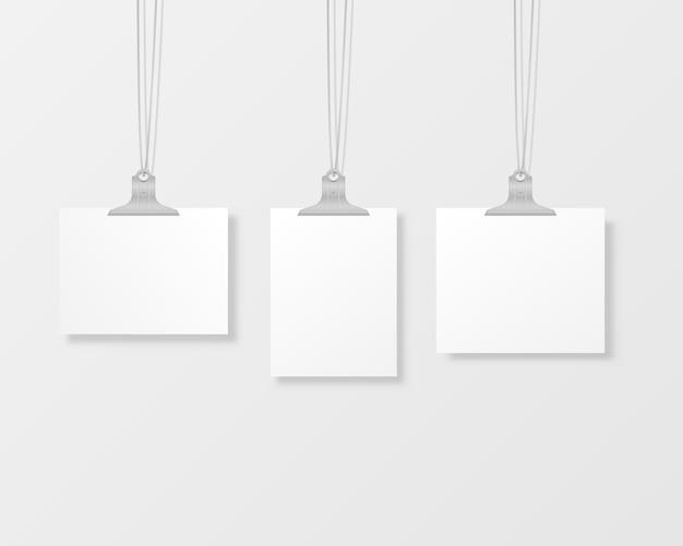 Marcos de fotos colgantes en blanco o plantillas de carteles aislados en el fondo. un conjunto de póster blanco colgado en una carpeta en la pared. marco para una hoja de papel.