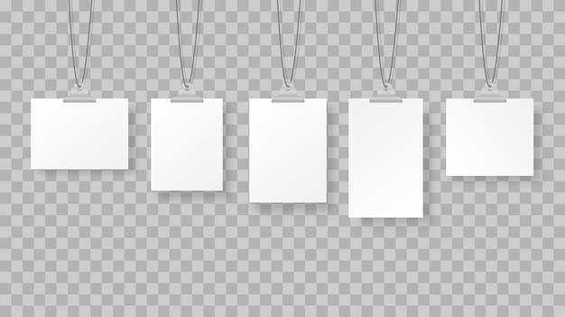 Marcos de fotos colgantes en blanco o plantillas de carteles en el fondo.