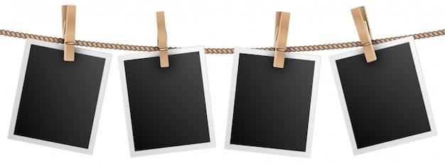 Marcos de fotos retro colgando de una soga aislado en blanco