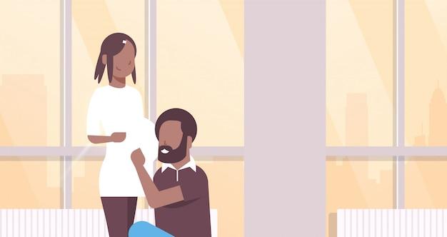 Marido escuchando embarazada esposa vientre pareja hombre mujer abrazando embarazo y paternidad