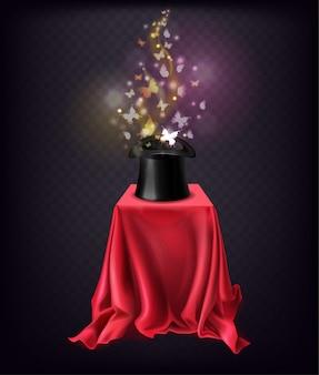 Mariposas brillantes volando desde un sombrero de copa negro de pie sobre un soporte cubierto con una capa de seda roja