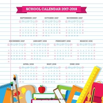 Material escolar y calendario sobre hoja de libreta