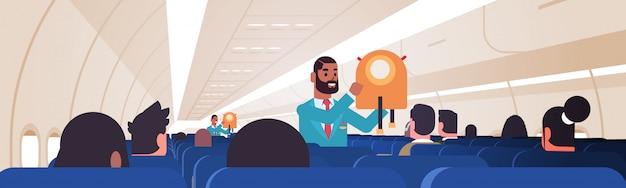 Mayordomo explicando a los pasajeros cómo usar el chaleco salvavidas en situaciones de emergencia asistentes de vuelo afroamericanos concepto de demostración de seguridad tablero de avión moderno interior plano horizontal