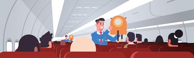 Mayordomo explicando a los pasajeros cómo usar el chaleco salvavidas en situaciones de emergencia asistentes de vuelo concepto de demostración de seguridad interior del tablero del avión moderno