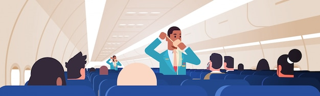 Mayordomo explicando a los pasajeros cómo usar la máscara de oxígeno en situaciones de emergencia asistentes de vuelo masculinos afroamericanos concepto de demostración de seguridad tablero del avión moderno interior