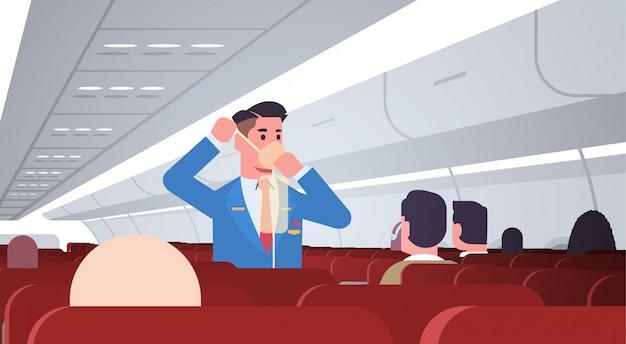 Mayordomo explicando a los pasajeros cómo usar la máscara de oxígeno en situaciones de emergencia concepto de demostración de seguridad de auxiliar de vuelo masculino moderno interior del tablero del avión