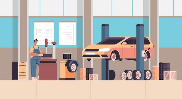 Mecánico en uniforme reparando llantas hombre trabajando y arreglando ruedas servicio de automóviles reparación de automóviles y chequear concepto estación de mantenimiento interior horizontal ilustración vectorial de longitud completa