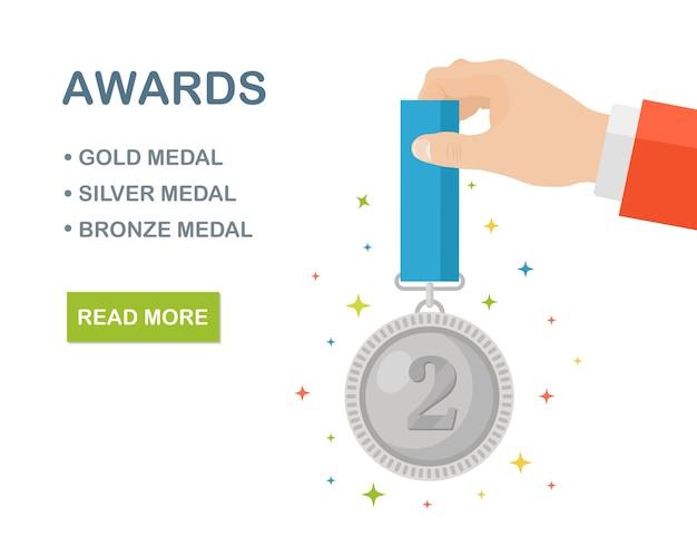 Medalla de plata con lazo azul para el segundo lugar en mano.