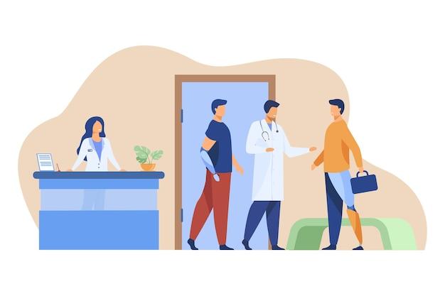 Médico examina a pacientes con miembros artificiales.