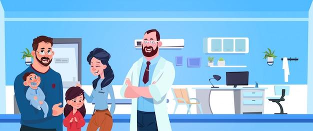 Médico de familia con padres felices y niños en la sala de pediatría del hospital
