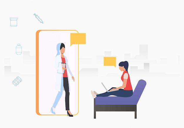 Médico saliendo del teléfono móvil a una mujer usando una computadora portátil