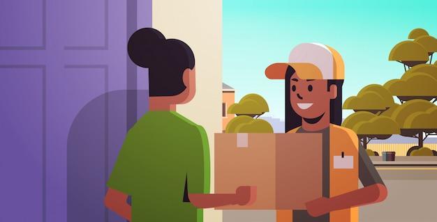 Mensajero mujer entrega caja de paquete de cartón a destinatario de niña afroamericana en concepto de servicio de entrega urgente en casa horizontal retrato