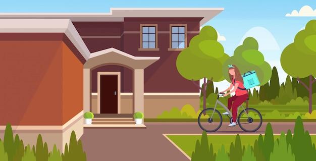 Mensajero de mujer con mochila grande montando bicicleta entregando comida de la tienda o restaurante concepto de servicio de entrega urgente villa moderna paisaje horizontal de fondo integral