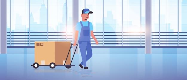 Mensajero en uniforme empujando la carretilla con caja de cartón servicio de entrega urgente concepto trabajador con carretilla de mano moderna oficina hall interior