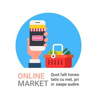 Mercado en línea mano que sostiene el teléfono inteligente que compra productos de la tienda de comestibles y concepto de la entrega de la comida