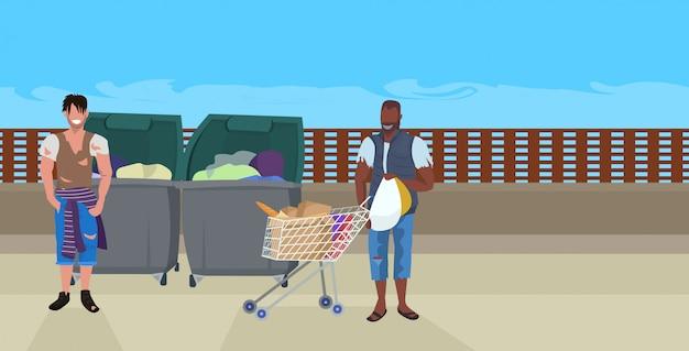 Mezcla de vagabundos de la raza en busca de comida y ropa en el bote de basura en la calle mendigo afroamericano empujando el carrito con pertenencias concepto de personas sin hogar horizontal de longitud completa