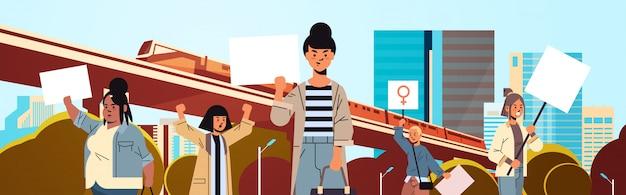 Mezclar activistas de raza sosteniendo pancartas con signo de género femenino manifestación feminista movimiento de poder femenino protección de derechos mujeres empoderamiento concepto retrato paisaje urbano fondo horizontal