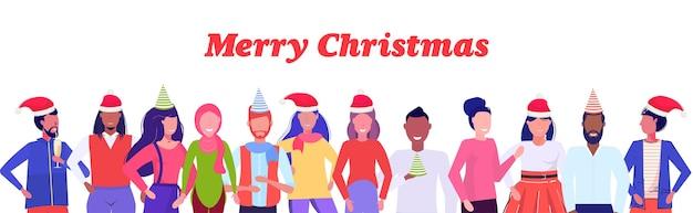 Mezclar gente de raza con sombreros de santa claus parados juntos gafas feliz navidad feliz año nuevo vacaciones de invierno celebración de fiestas corporativas