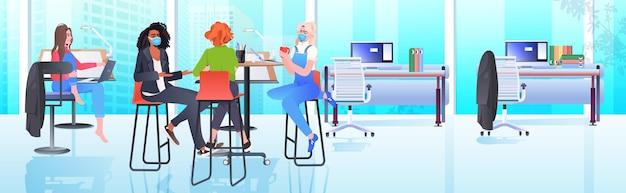 Mezclar mujeres empresarias de raza en máscaras trabajando y hablando juntas en el centro de coworking concepto de trabajo en equipo de la pandemia de coronavirus moderno interior de la oficina horizontal