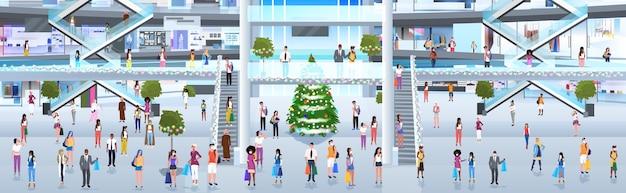 Mezclar personas de raza en máscaras caminando en el centro comercial con compras cerca del árbol de navidad celebración de vacaciones de año nuevo concepto de cuarentena de coronavirus ilustración de cuerpo entero