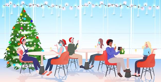 Mezclar personas de raza en máscaras sentadas en mesas de café amigos con sombreros de santa discutiendo durante la reunión ilustración de vector de longitud completa horizontal interior moderno restaurante
